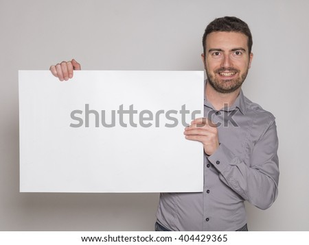 young man holding a white copyspace billboard on gray background - stock photo