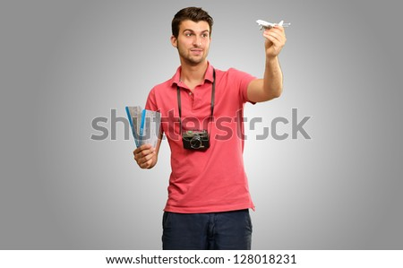 Young Man Holding Airplane And Boarding Pass Isolated On Grey Background - stock photo