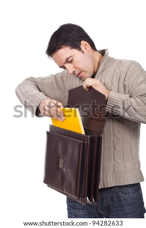young man holding an open briefcase and putting a document inside - stock photo