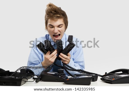 Young man holding and yelling to the phones - stock photo