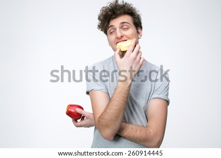 Young man holding apple and eating unhealthy donut - stock photo