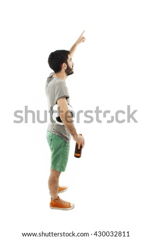 Young man holding ball and beer, pointing. Isolated on white background - stock photo