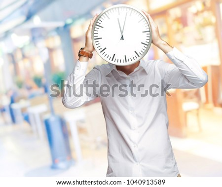Young Man Holding Big Clock Covering His Face, Indoor