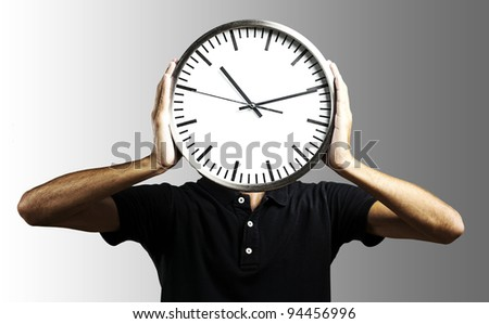 young man holding big clock covering his face over grey - stock photo