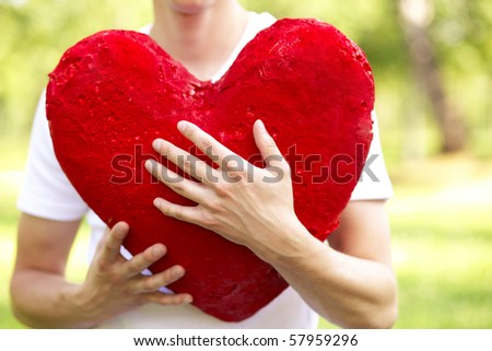 young man holding big red heart outdoor - stock photo