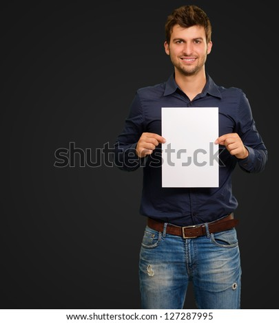 Young Man Holding Blank Paper On Black Background - stock photo