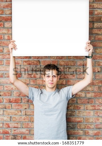 Young man holding blank whiteboard on business presentation - stock photo