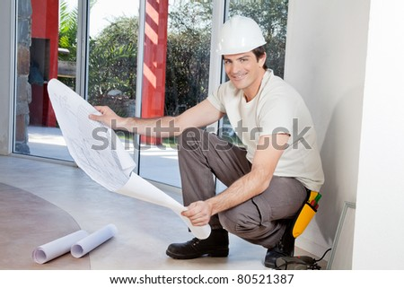 Young man holding blueprint and smiling - stock photo