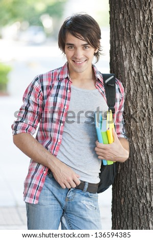 Young man holding books on the street.