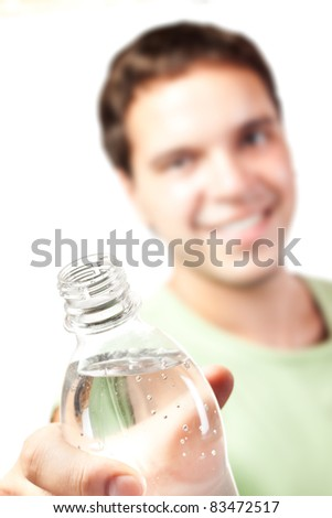 young man holding bottle of water isolated on white background. focus on bottle - stock photo