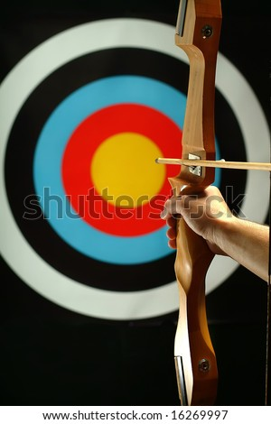 Young man holding bow and shooting to target - stock photo