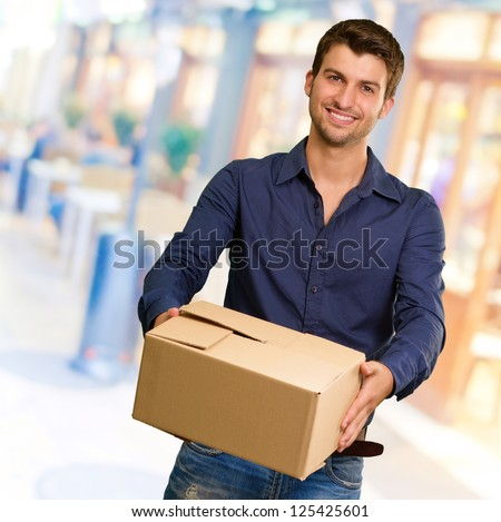 Young Man Holding Card box, Indoors - stock photo