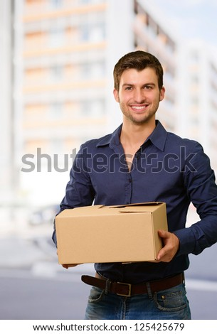 Young Man Holding Card box, Outdoors