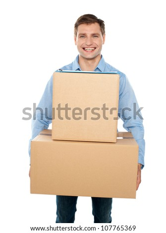 Young man holding cardboard boxes and smiling at the camera