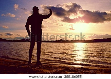 Young man holding cellphone, taking picture of autumn sunset or sunrise in picturesque sea scenery
