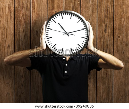 Young man holding clock against a wooden wall - stock photo