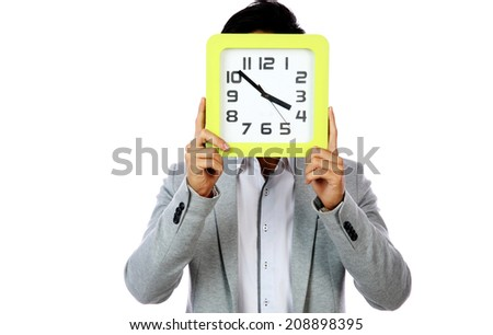 Young man holding clock covering his face over white background