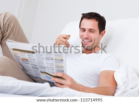 Young Man Holding Cup In Hand Reading Newspaper, Indoors - stock photo
