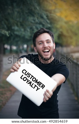 Young man holding Customer Loyalty sign