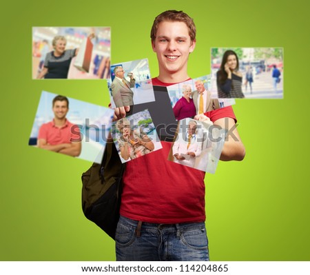 Young Man Holding Digital Tablet With Photos On Green Background - stock photo
