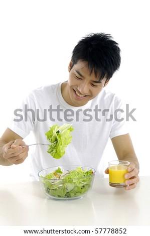 Young man holding fresh salad with orange juice - stock photo