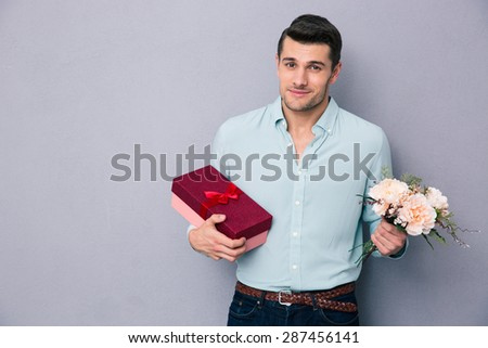Young man holding gift box and flowers over gray background. Looking at camera - stock photo