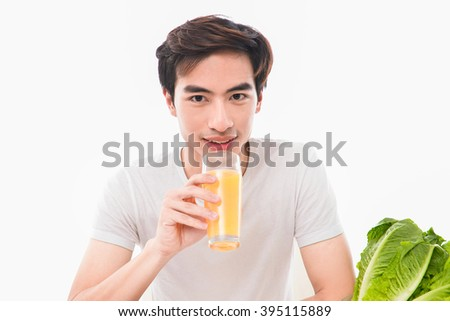 young man holding glass of orange juice - stock photo