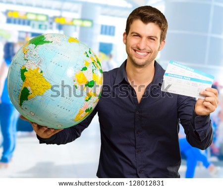 Young Man Holding Globe And Boarding Pass, Indoors - stock photo