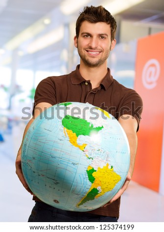 Young Man Holding Globe, Indoors - stock photo