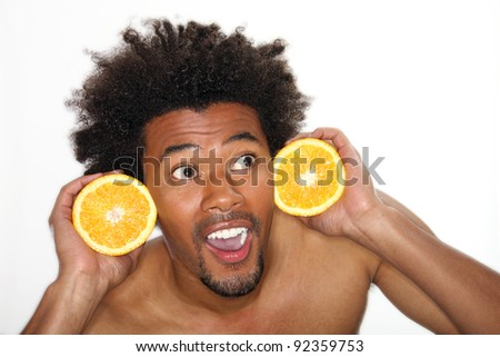 Young man holding halves of orange - stock photo