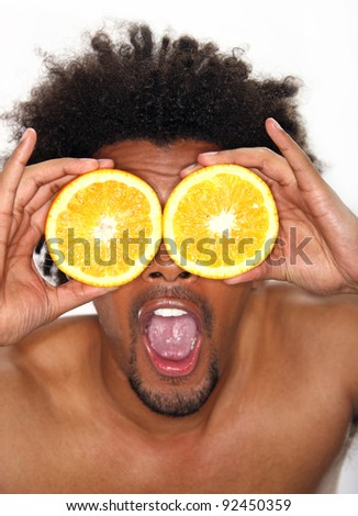 Young man holding halves of oranges in front of his eyes - stock photo