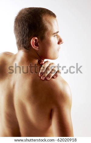 Young man holding hand on shoulder - stock photo