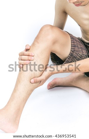 Young man holding his calf muscle in pain, isolated on white background