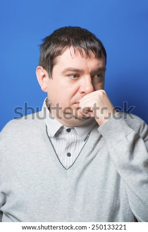 young  man holding his chin on his hand looking at the camera - stock photo