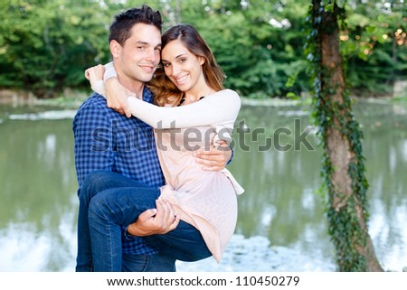 Young man holding his girlfriend by the pond - stock photo