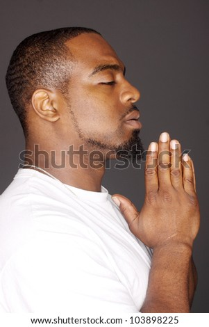 Young man holding his hands in prayer.
