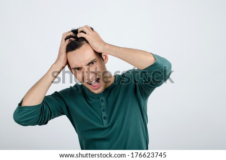 Young man holding his head frowning with worry screaming. Man pulling his hear for worry, sadness, desperation. Man with different facial expressions. - stock photo