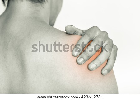 Young man holding his shoulder in pain, isolated on white background, monochrome photo - stock photo