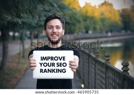 Young man holding  Improve Your Seo Ranking sign