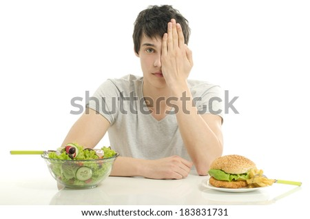 Young man holding in front a bowl of salad and a big hamburger. Choosing between good healthy food and bad unhealthy food - stock photo