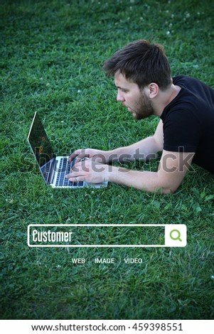 Young man holding laptop writen Customer on it - stock photo