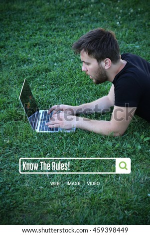 Young man holding laptop writen Know The Rules! on it - stock photo