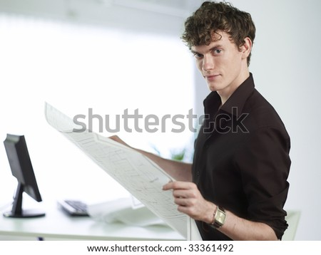 Young man holding large documents in office - stock photo
