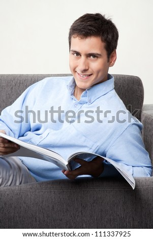 Young man holding magazine on couch.
