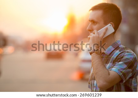 Young man holding mobile phone, using smartphone, making a call, talking on the phone, standing on sunny street with transport traffic on the background - stock photo