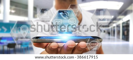 Young man holding mobile phone with application icons interface in his hand - stock photo