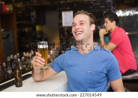 Young man holding pint of beer at the bar