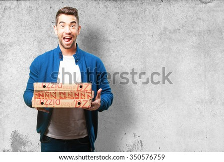 young man holding pizzas - stock photo