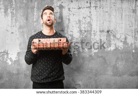 young man holding pizzas