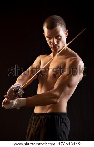 Young Man Holding Samurai Sword on Black Background. - stock photo